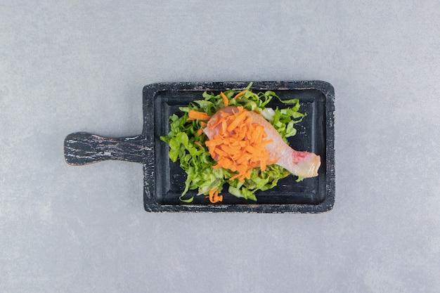Carote e verdure saporite con coscia di pollo sulla tavola, sulla superficie bianca