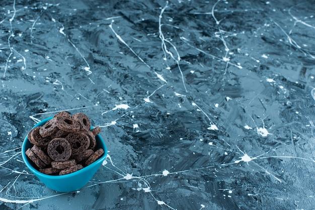 대리석 배경에 그릇에 맛있는 초콜릿 코팅 된 옥수수 반지.