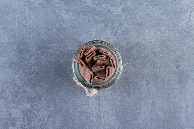 Flavorful chocolate wafer roll in a jar on the marble surface