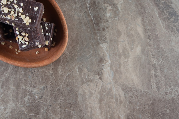 Cialda al cioccolato saporita su una ciotola di argilla su marmo.