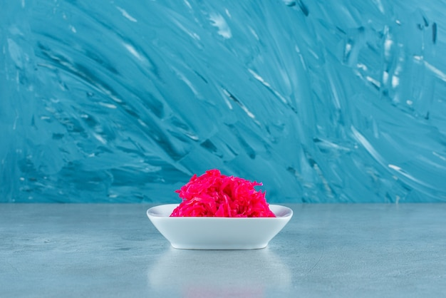 Вкусная нарезанная красная квашеная капуста в миске на синем столе.