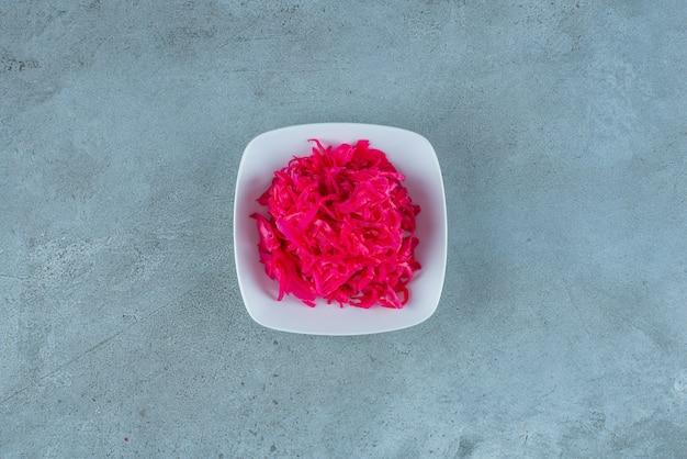 파란 탁자 위에 있는 그릇에 있는 맛있는 다진 붉은 발효 소금에 절인 양배추.