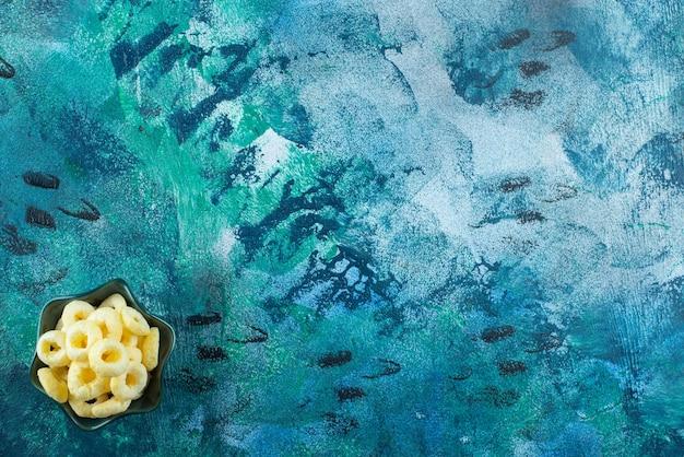 青いテーブルの上に、ボウルに風味豊かなトウモロコシの指輪があります。