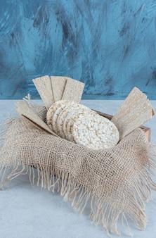 Fette biscottate saporite su asciugamano nella scatola su marmo.