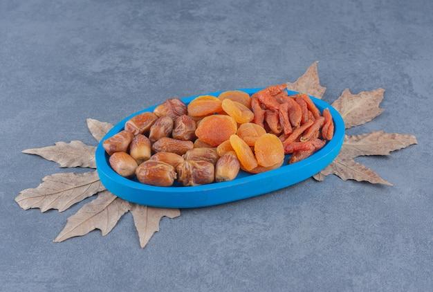大理石の背景のトレイにある風味豊かなドライフルーツ。