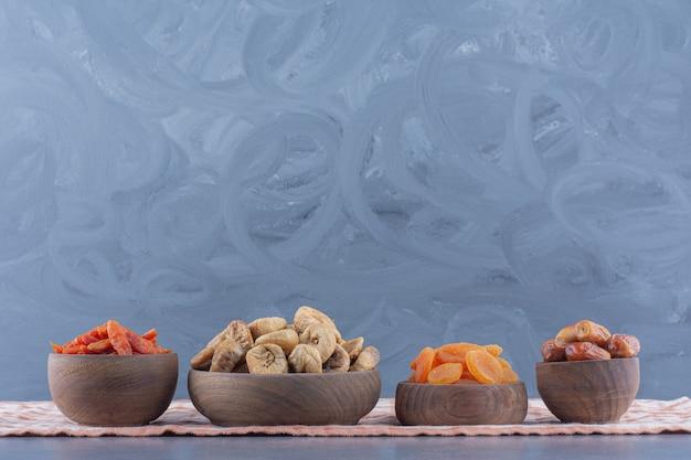 Frutta secca saporita in ciotole sull'asciugamano, sullo sfondo di marmo.