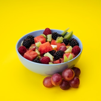 Flavorful fruit salad on yellow background