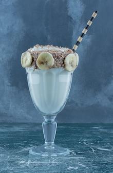 青い背景にバナナのかけらと風味豊かなミルクセーキ。高品質の写真