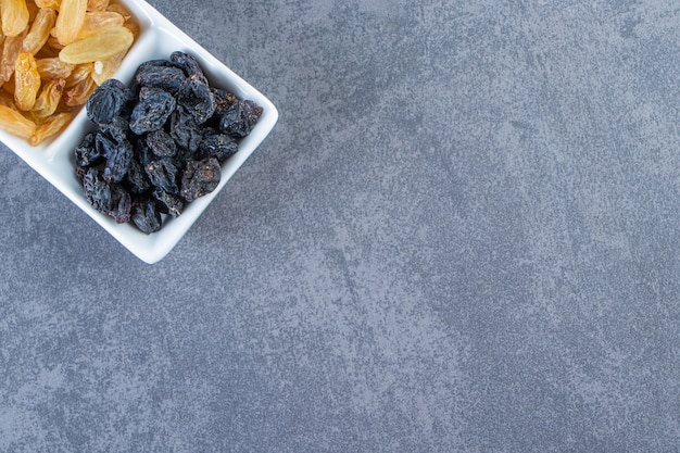 Flavorful raisins on a dish , on the marble background.