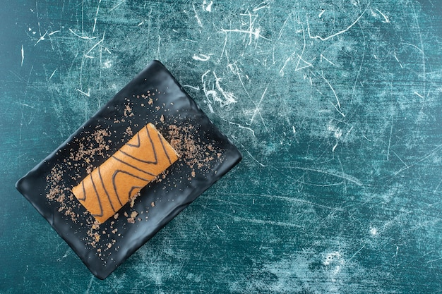 Flavorful roll cake on a black plate , on the blue background. high quality photo