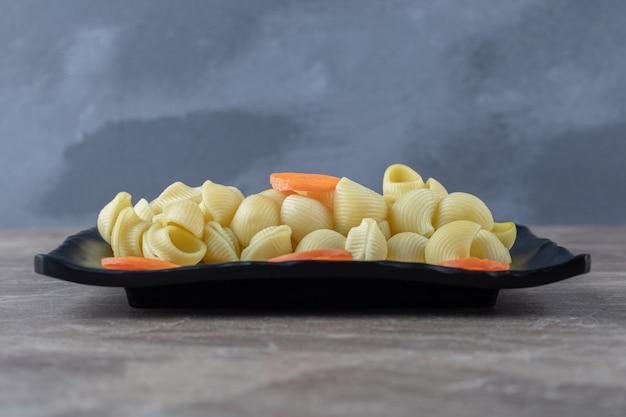 Carote affettate saporite accanto agli spaghetti, sul piatto di legno, sulla superficie di marmo.
