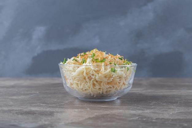 대리석 표면에 그릇에 녹색 채소를 넣은 풍미있는 당면 파스타.