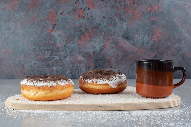 Flavorous donuts and a cup of tea with a snowflake decoration, on a board with sprinkled coconut powder on marble surface