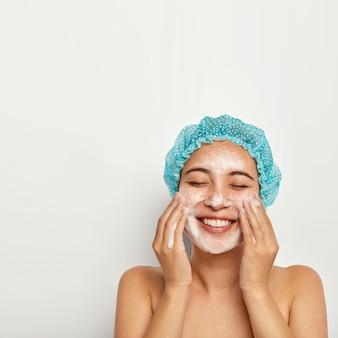 完璧で純粋な肌。きれいな女性の縦の画像は、顔を洗い、冷たい水を楽しみ、肌に泡を持ち、嬉しそうに笑い、目を閉じて、個人の衛生管理をします。ウェルネスコンセプト