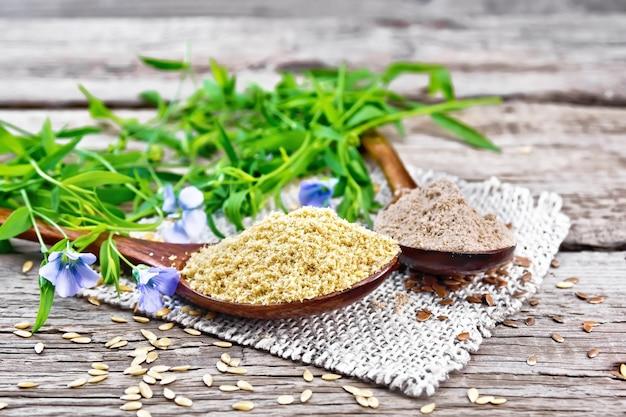 黄麻布のナプキンに2つのスプーンで亜麻のふすまと小麦粉、木の板の背景にリネンの葉と花