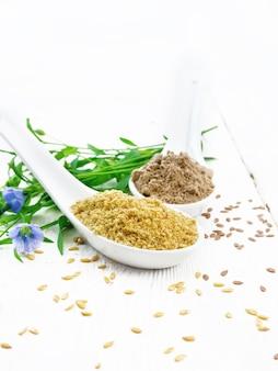 2つのスプーンで亜麻のふすまと小麦粉、テーブルの上の種子、亜麻の葉と明るい木の板の背景に花