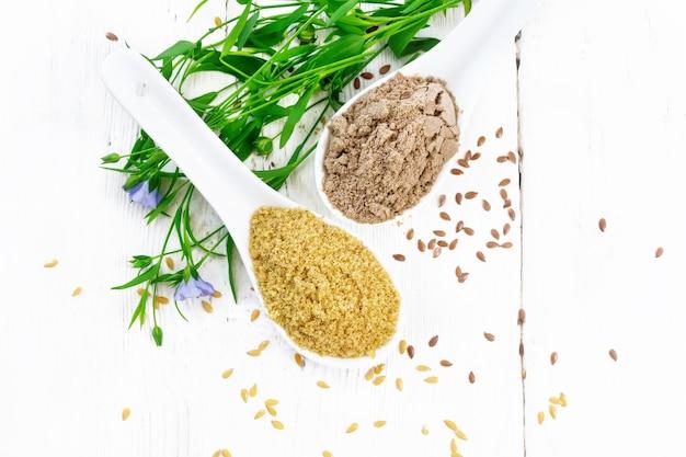 2つのスプーンで亜麻のふすまと小麦粉、テーブルの上の種子、上から木の板の背景に亜麻の葉と花