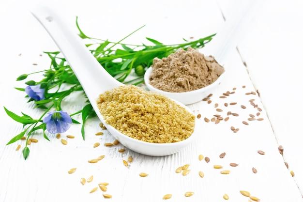 2つのスプーンで亜麻のふすまと小麦粉、テーブルの上の種子、白い木の板の背景に亜麻の葉と花