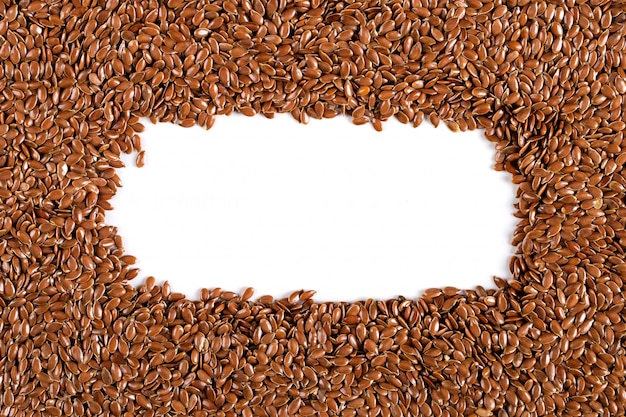 Flax grains uniformly scattered in the form of a frame, yellow  made of spices. , copyspace.