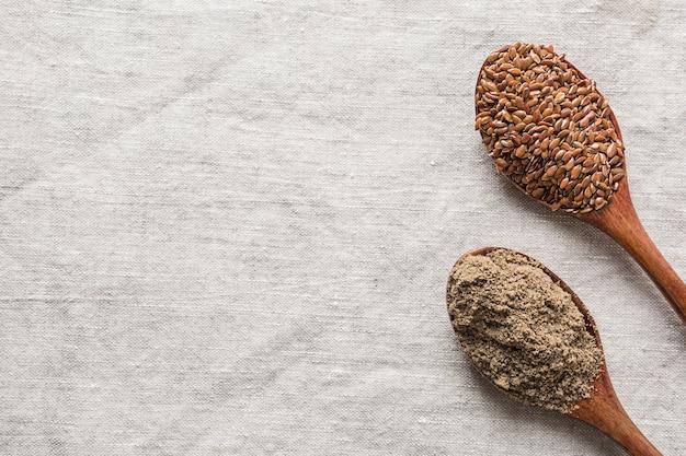 亜麻の種子とリネンのテーブルクロスに木製のスプーンで小麦粉。上からの眺め。テキストのためのスペース。