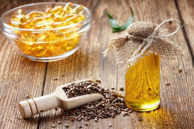 Семена льна и масло в бутылке на деревянных фоне