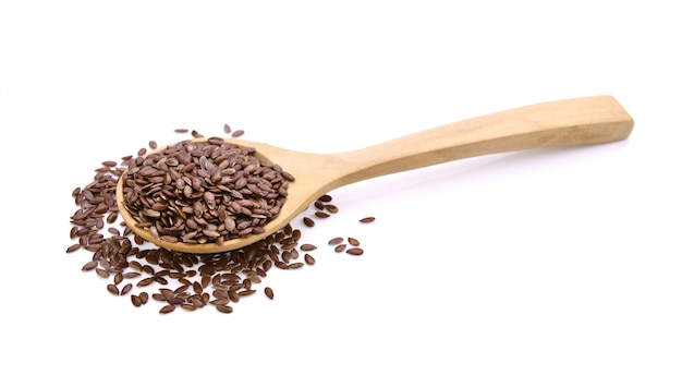 Flax seeds heap in wood spoon on white space