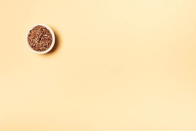 Семена льна в банке на желтом фоне с копией пространства