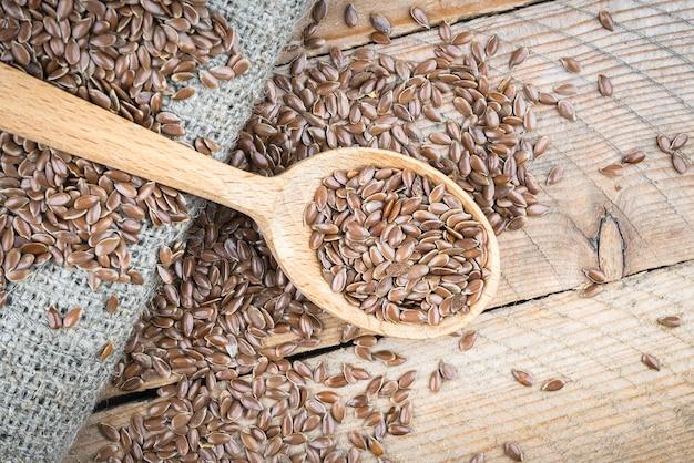 Семена льна в деревянной ложке на льняной ткани