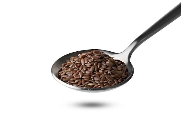 Семена льна в железной ложке, изолированные на белой поверхности
