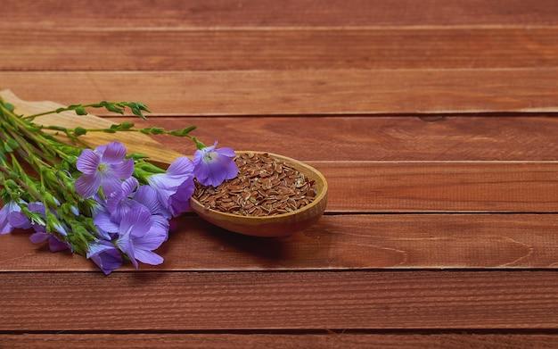 茶色のヴィンテージの背景に亜麻の植物と林の花とヴィンテージスプーンで亜麻の種子。医学と食事栄養のための概念的な写真。