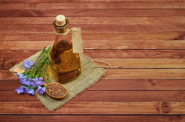 木のスプーンの亜麻仁、花と亜麻仁油の亜麻仁油、木製の背景にヴィンテージの荒布をガラス瓶に。医学と食事栄養のための概念的な写真。
