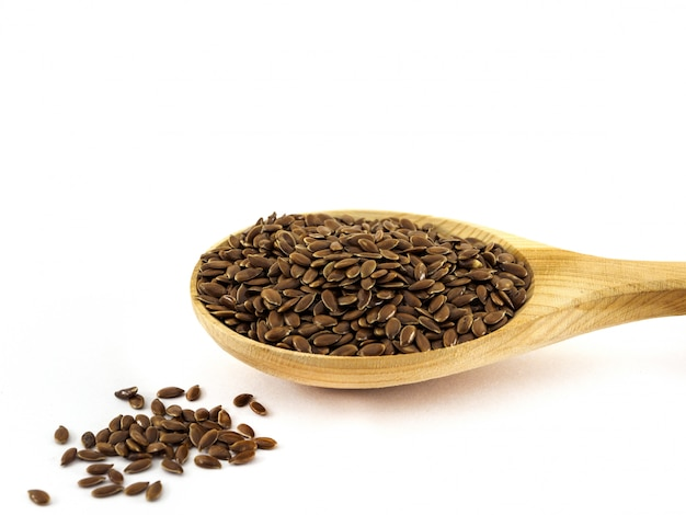 Flax seeds lie in a wooden spoon on a white
