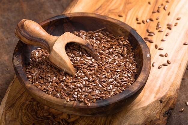 Flax seeds or line in bowl on wooden table
