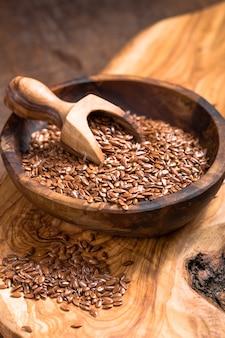 Семена льна или линия в миску на деревянный стол