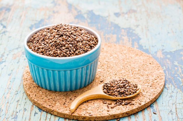 Flax seeds in a spoon and  a bowl on a wooden table
