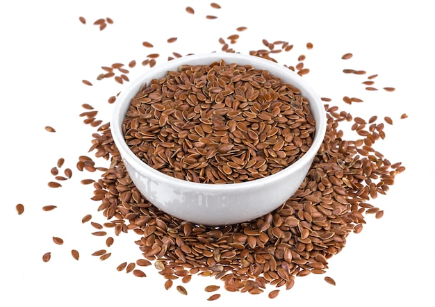 Flax seeds in wooden bowl isolated on white background close up