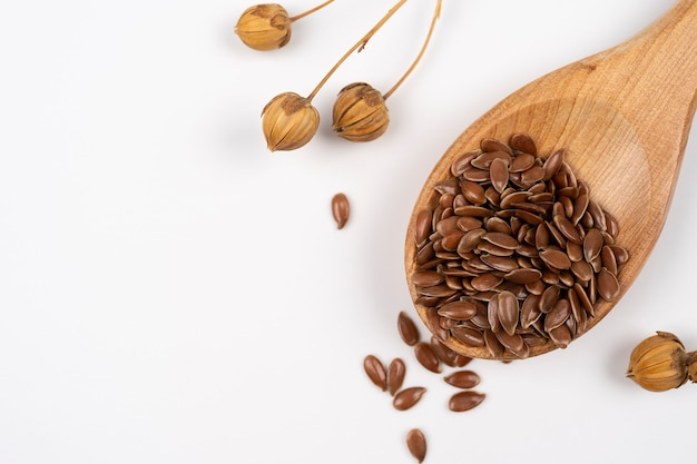 Flax seeds in a wooden spoon linen seed is scattered from spoon on a white backdrop flax plant