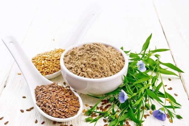 ボウルに亜麻仁粉、2つのスプーンとテーブルに白と茶色のリネンの種、白い木の板の背景に亜麻の葉と花