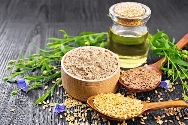 ボウルに亜麻仁粉、2つのスプーンとテーブルに白と茶色の種子、亜麻の葉と花、木の板の背景にガラスの瓶に油