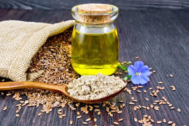 スプーンの亜麻仁粉、ガラスの瓶の油、青いリネンの花、暗い木の板の背景にバッグの茶色の種子