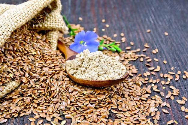 スプーンの亜麻仁粉、バッグとテーブルの上の種子、木の板の背景に青いリネンの花