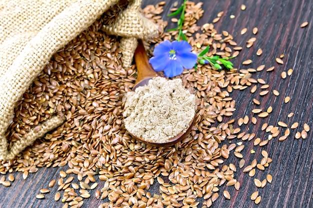 スプーンの亜麻仁粉、バッグとテーブルの上の種子、木の板の背景にリネンの花