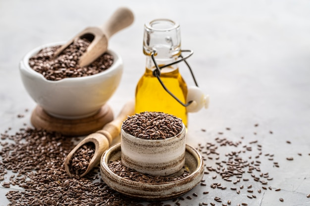 Flaxseed oil in a bottle and ceramic bowl with brown flax seeds and wooden spoon on a white