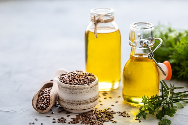 Flaxseed oil in a bottle and ceramic bowl with brown flax seeds and wooden spoon
