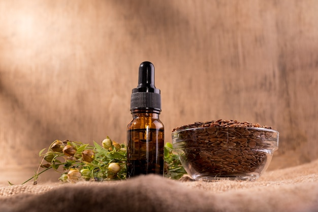 Flaxseed oil cosmetic bottle. composition with dispenser bottle, flax seeds, and plants on sackcloth.