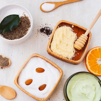 Flay lay of body butter with almonds on wooden table