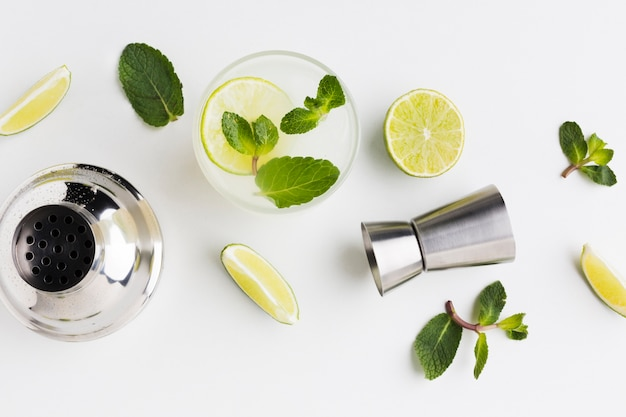 Flay lay of cocktail essentials with lime and shaker