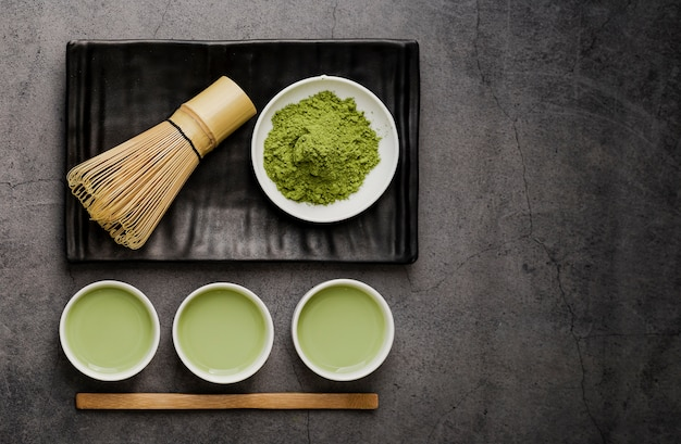 Flay lay of cups of matcha tea with bamboo whisk and copy space