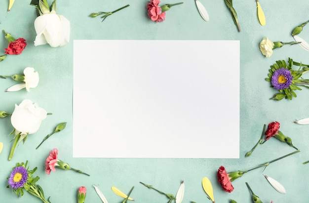 Flay lay frame of carnation flowers with white card