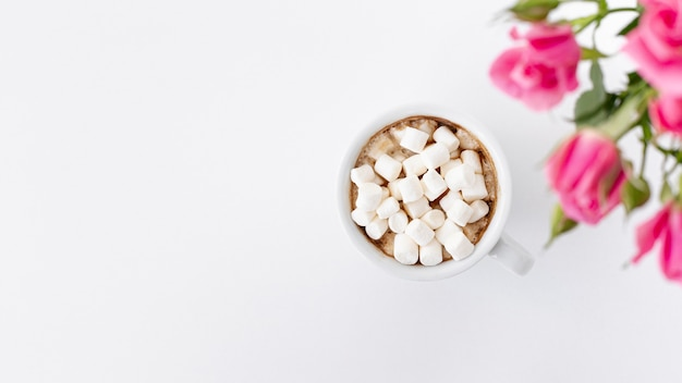 Flay lay of marshmallow cup with roses and copy space